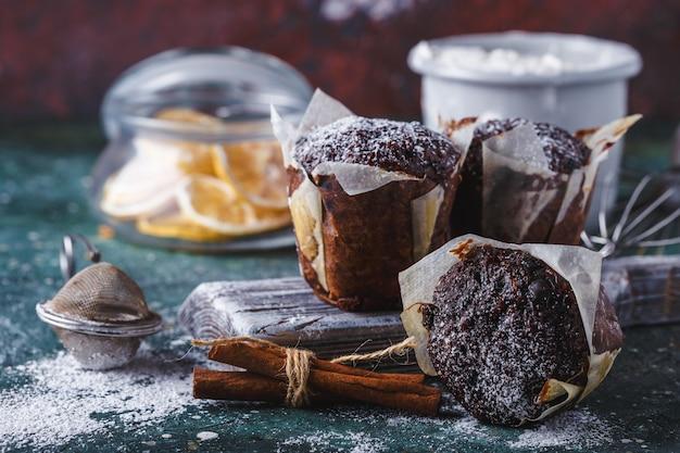 Wortel-chocolademuffin bestrooid met poedersuiker, een kopje thee, bakselingrediënten. bloem, eieren, citroencitrus op een donkere tafel