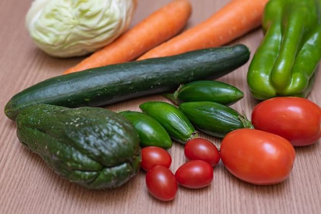 Wortel, kool, komkommer, chayote, tomaat en paprika op tafel