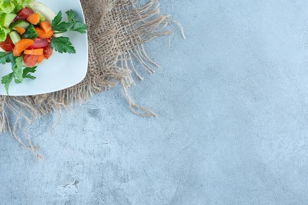 Wortel, paprika, komkommer, plakjes sla en peterselieblaadjes in een saladeplateau op marmeren tafel.