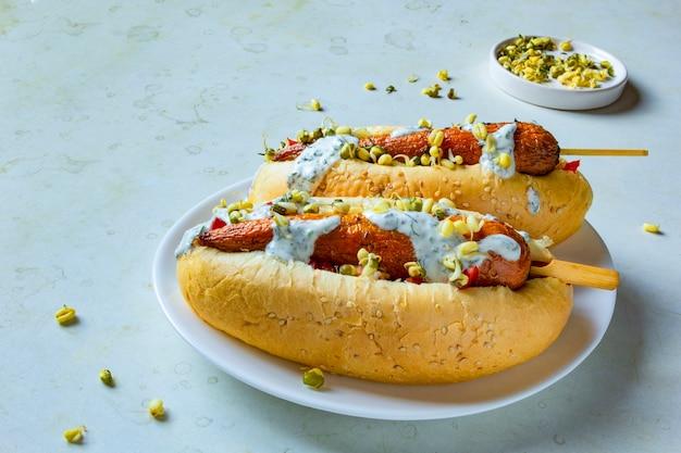 Wortel veganistische hotdog. witte plaat met vegetarisch straatvoedsel. gezond plantaardig vleesloos maaltijdconcept.