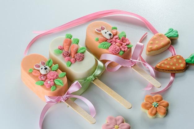 Wortelcake cakeicles, gedecoreerd met konijn, bloemen en strik. naast wortel- en bloemvormige koekjes