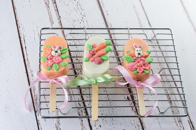 Wortelcake cakeicles, gedecoreerd met konijn, bloemen en strik. op een metalen rooster.
