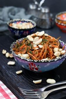 Wortelsalade met pinda's in oosterse stijl in een kom tegen een donkere