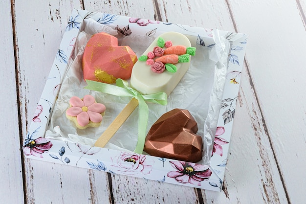 Worteltaart cakeicle omgeven door hartvormige chocolade en bloemvormig koekje. op een witte doos.