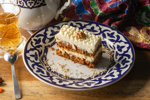 Worteltaart. dessert van biscuitgebak met walnoten gedrenkt in botercrème in een bord met een nationaal oezbeeks ornament