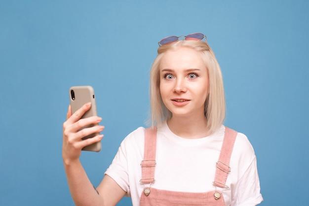 Woteenager met een smartphone in haar handen op blauw
