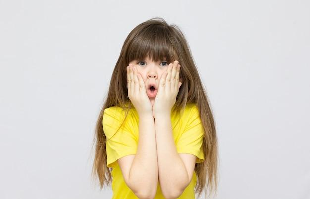 Wow close-up van een knap meisje met donkerbruin haar en blauwe ogen die de hand op de wang houden, opzij kijkend met een dromerige uitdrukking.