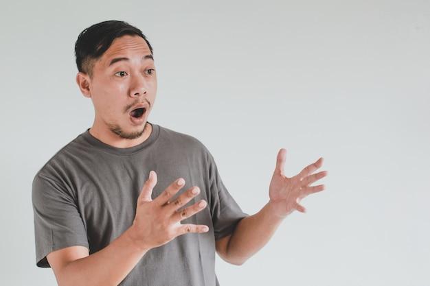 Wow en geschokte gezichtsuitdrukking van aziatische man wijzen op een lege ruimte met inhoud advertentiemodelconcept