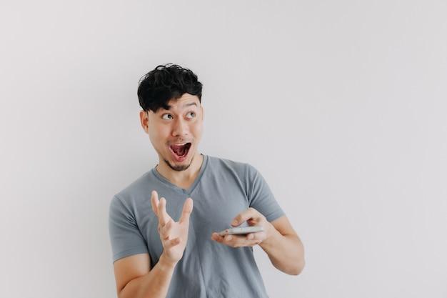 Wow en verrast gezicht van de mens houdt een smartphone vast die op een witte muur is geïsoleerd