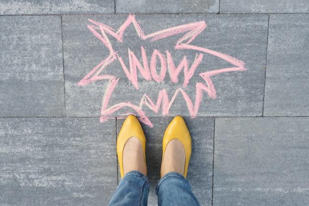 Wow geschreven op grijze stoep met benen van de vrouw in de voeten in gele schoenen