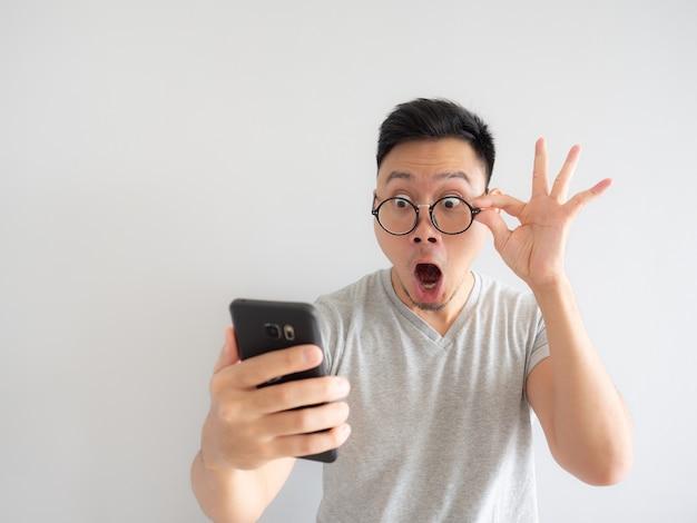 Wow-gezicht van de man schokte wat hij op de smartphone ziet.