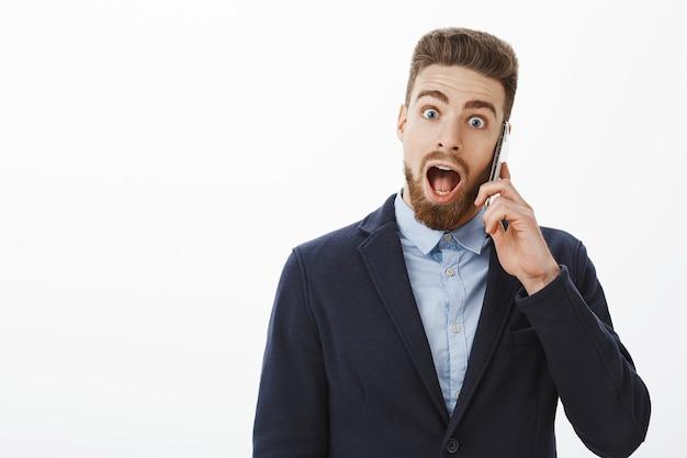 Wow, mijn bedrijf heeft nog een miljoen opgehaald. opgewonden en verbaasd knappe volwassen man met blauwe ogen en baard in formeel pak met smartphone in de buurt van oor schokkende details leren, verbaasd verbaasd laten vallen
