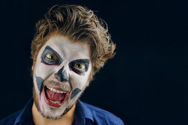 Wreed kijkt, schreeuwt of lacht. make-up man met grote groene ogen van de dag van de dood op halloween. kopieer ruimte