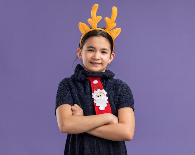 Wrokkig meisje in gebreide jurk rode stropdas met grappige rand met hertenhoorns op hoofd met gekruiste armen over paarse muur