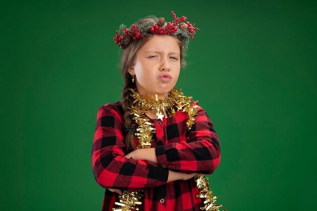Wrokkig meisje kerstkrans dragen in gecontroleerde jurk met klatergoud rond nek camera kijken met fronsend gezicht met gekruiste armen staande over groene achtergrond