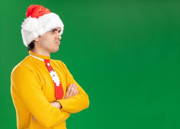 Wrokkige jonge man in gele coltrui en kerstmuts met grappige stropdas opzij kijken ontevreden met gekruiste armen en permanent over groene achtergrond