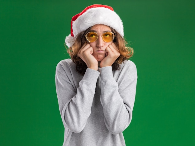 Wrokkige jonge man met een kerstmuts en een gele bril die omhoog kijkt en wangen opblaast die over de groene muur staan