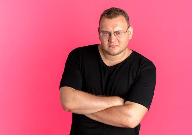Wrokkige man met overgewicht in glazen met zwart t-shirt met fronsend gezicht met gekruiste armen over roze