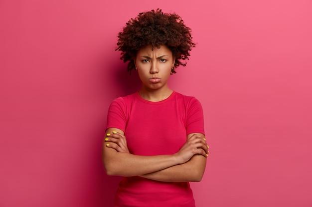 Wrokkige, ongelukkige vrouw kijkt met een norse grimas, kruist de armen over het lichaam, ontevreden over slechte behandeling, kijkt boos, draagt een rood t-shirt, poseert over roze muur. negatieve emoties