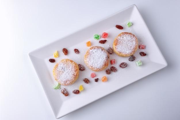 Wrongel pannenkoeken met rozijnen en gekonfijte vruchten op een witte plaat bovenaanzicht