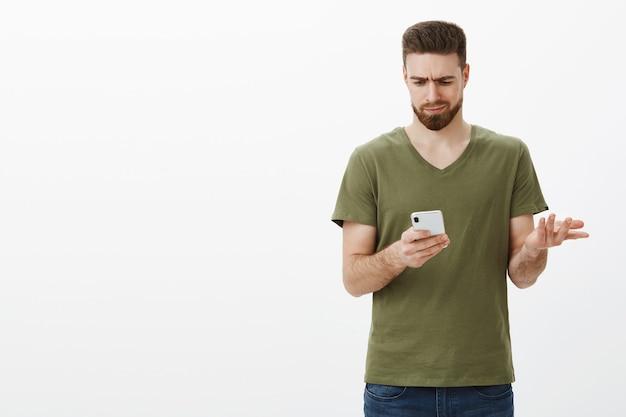 Wtf deze emoji betekent. verward somber en onrustig aantrekkelijk vriendje fronst terwijl hij boos en onwetend naar het scherm van de smartphone kijkt, zijn hand opheft van ontzetting, probeert te begrijpen wat er geschreven staat