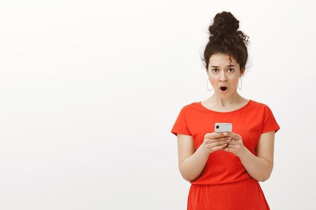 Wtf die dit bericht heeft geschreven. portret van geschokt ontevreden charmante vrouwelijke vrouw in rode jurk