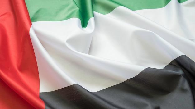 Wuivende stoffentextuur van de vlag met de kleur van de verenigde arabische emiraten, de echte textuurvlag van de vae