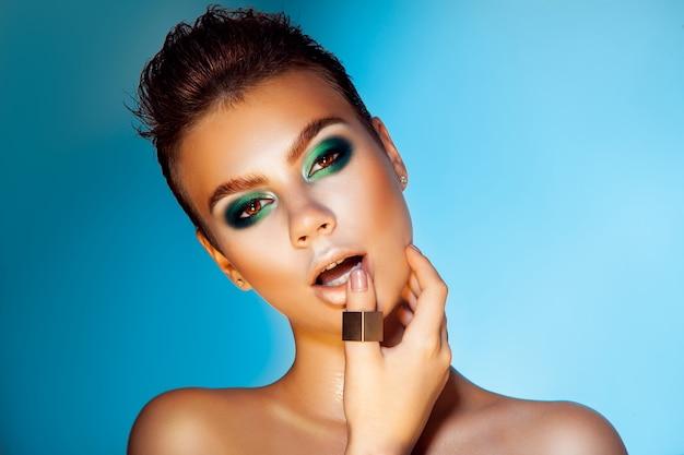 Wulpse volwassen vrouw met groene kleuren make-up op blauwe achtergrond kijken camera studio shot