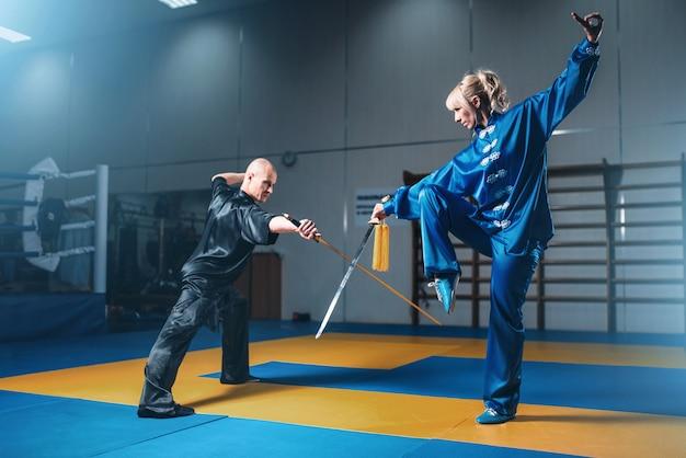 Wushu-strijders, man en vrouw met zwaarden, martial arts-cultuur