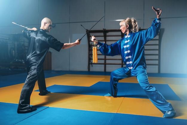 Wushu-strijders, man en vrouw met zwaarden