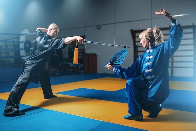 Wushu-strijders, man met zwaard en vrouw met waaier, krijgskunstcultuur