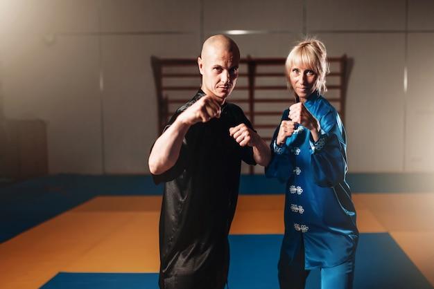 Wushu-strijders, mannelijke en vrouwelijke partners vormen een indoor, martial arts-cultuur