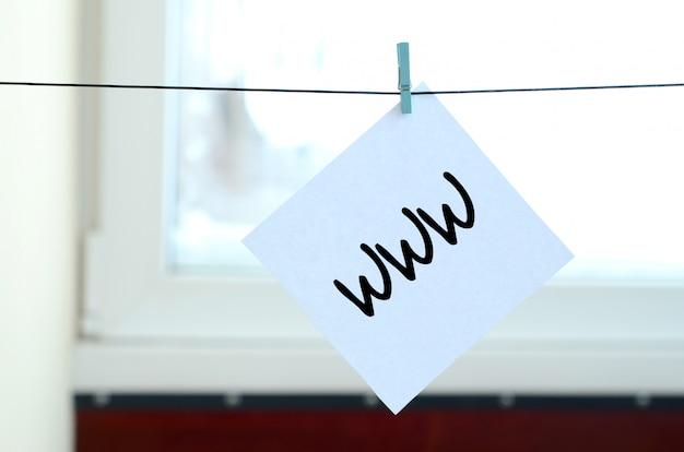 Www. opmerking is geschreven op een witte sticker die met een wasknijper aan een touw op een achtergrond van vensterglas hangt