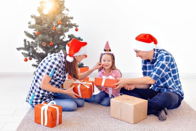 X-mas en vakantie concept - familie opening kerstcadeau voor boom.