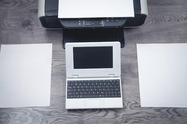 Xerox printer machine, laptop en papieren op het bureau.