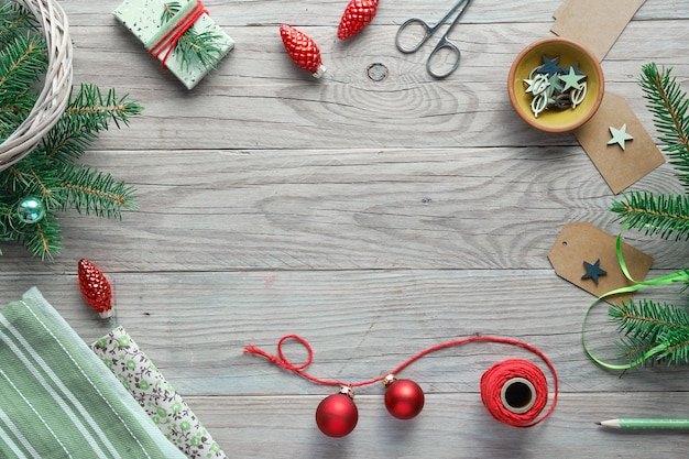 Xmas achtergrond met kerstboom fir twijgen, geschenkdozen en decoraties in rood en groen. handgemaakte diy decoraties.