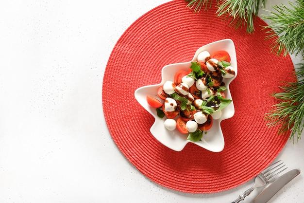 Xmas caprese salade geserveerd in plaat als kerstboom voor een feestelijk kerstfeest. uitzicht van boven.