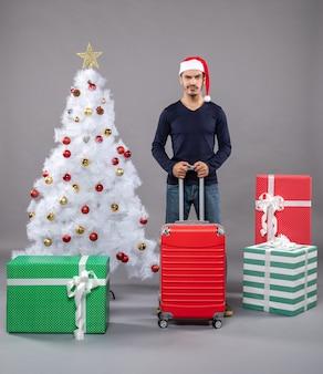 Xmas man met rode valise in de buurt van witte kerstboom met kleurrijk xmas speelgoed op
