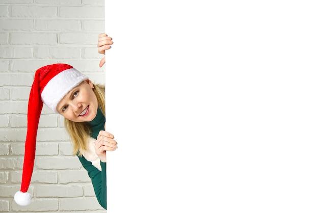 Xmas santa blonde vrouw gluren van achter leeg teken billboard toewijzen witte bakstenen muur. kerstmis-