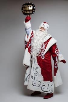 Xmas senior man in santa kostuum met feestelijke gelukkig nieuwjaar ballon
