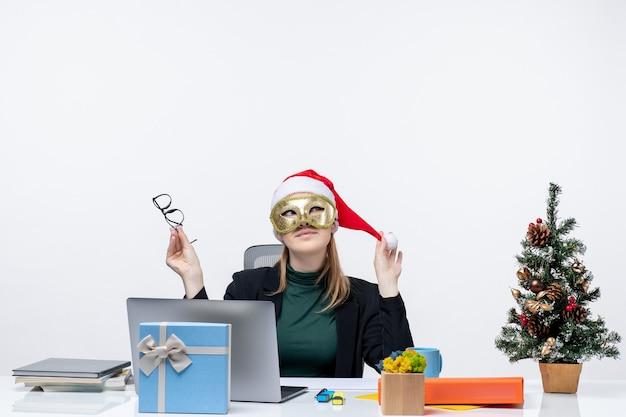Xmas stemming met dromerige jonge vrouw spelen met kerstman hoed houden bril en dragen masker zittend aan een tafel op witte achtergrond