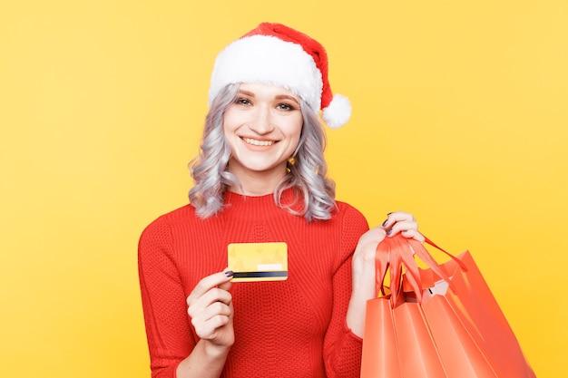 Xmas winkelen online concept. kerst meisje met creditcard en grote tassen.