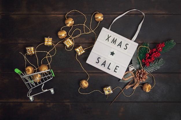 Xmass sale woord op lightbox en klein winkelwagentje met gouden geschenken op houten achtergrond.
