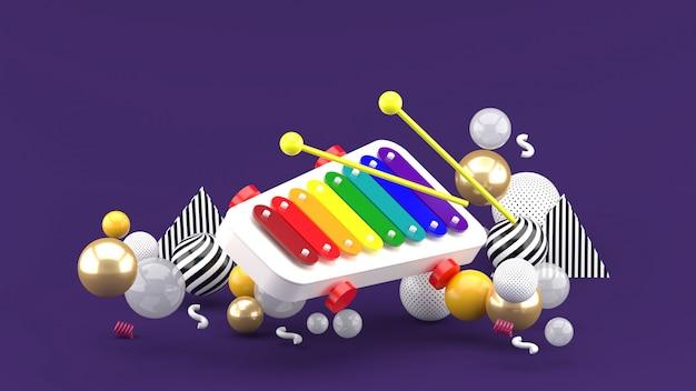 Xylofoon speelgoed onder kleurrijke ballen op paarse ruimte