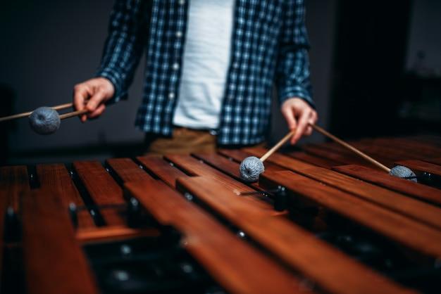 Xylofoonspelerhanden met stokken, houten geluiden