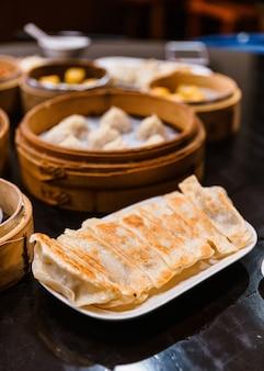 Yaki-gyoza set (japanse pan-fried dumplings) geserveerd op een wit bord met xiao long bao in een bamboestoomboot.