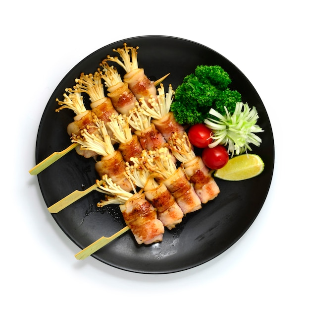 Yakitori gegrild spek en gouden naald paddestoel verpakte spiesjes