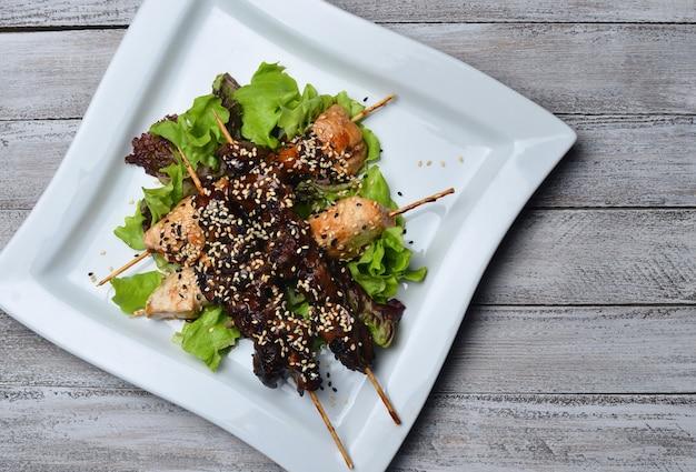Yakitori met sesamzaadjes op een plaat. gebakken kippenvlees en kippenlever op stokken op een houten tafel.