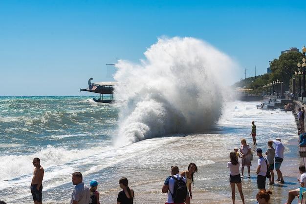 Yalta, crimea - 10 augustus 2018: storm in yalta, het breken van enorme golven in de buurt van dijk. stormachtige zee. razende zwarte zee. grote zeegolfplons tegen stadsdijk. gevaarlijk en krachtig natuurconcept.
