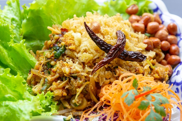 Yam naem khao thot is spicy salad of curried rice croquettes